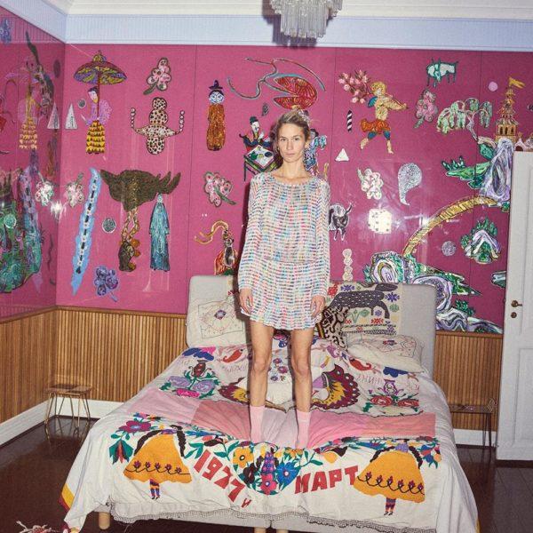 Lustre de Murano sobre a cama com colcha marroquina. O painel de vidro sobre parede rosa é obra de Tal R, noivo de Emma, que faz pose para o fotógrafo Philip Messmann