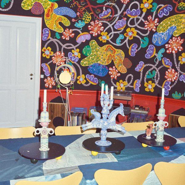 A pintura de Tal R cobre as paredes. Cadeiras Arne Jacobsen e candelabros Bjørn Wiinblad