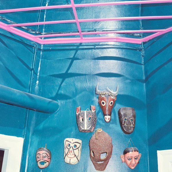 No hall interno, máscaras e parede azul