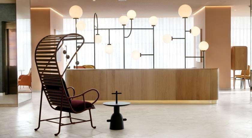O lobby, simples e chique, com madeira clara e mobiliário assinado
