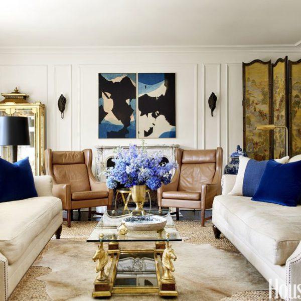 O living, claro e arejado recebe mobiliário em tons neutros e pontos de cor. Móveis antigos e a boiserie dão o tom!