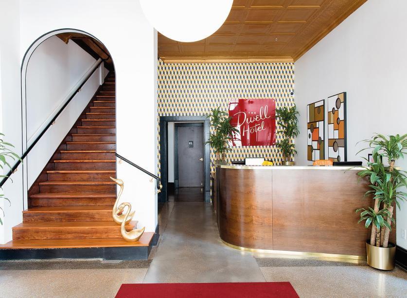 O hall de entrada com escada original da construção. O arco está de volta nos projetos mais legais. Anote!