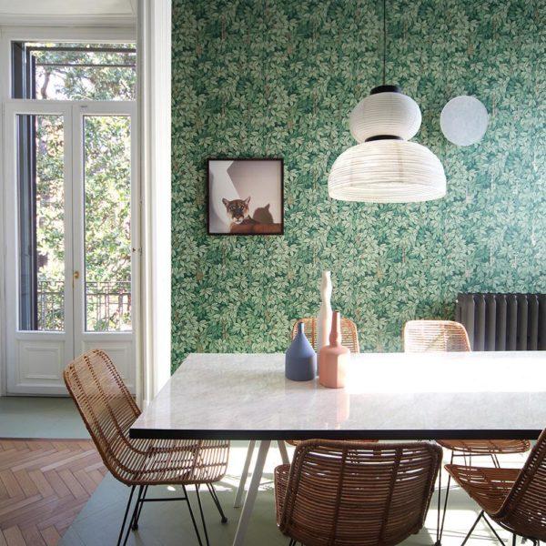 Mesa com tampo de fórmica e cadeiras em fibra natural fazem bonito combinadas ao papel de parede verde