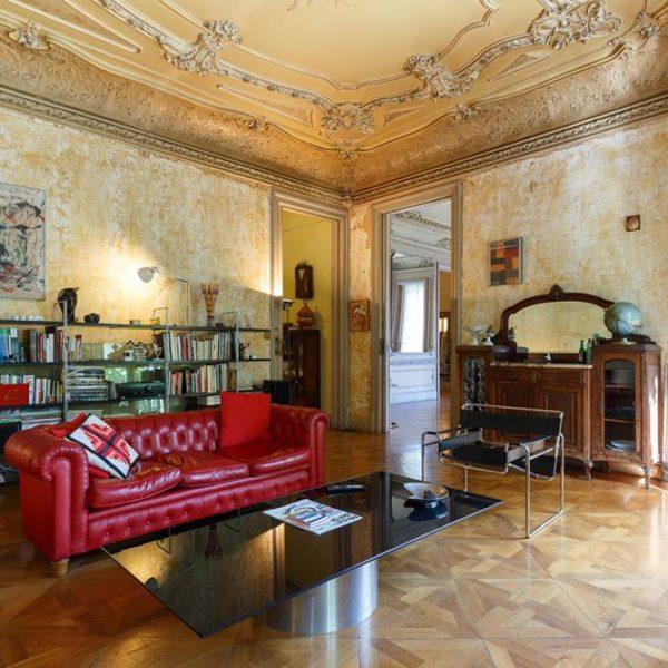 O teto ricamente decorado faz contraste com o sofá capitonê vermelho e a poltrona Wassily, desenhada pelo húngaro Marcel Breuer entre os anos de 1925 e 1927