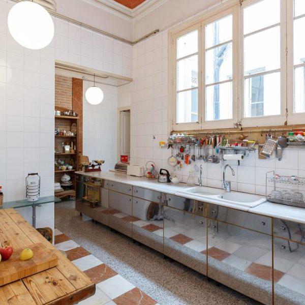 A cozinha recebeu bancada e azulejos brancos, bem ao estilo da época da construção, e armários revestidos em material padrão inox, que atualiza o conjunto