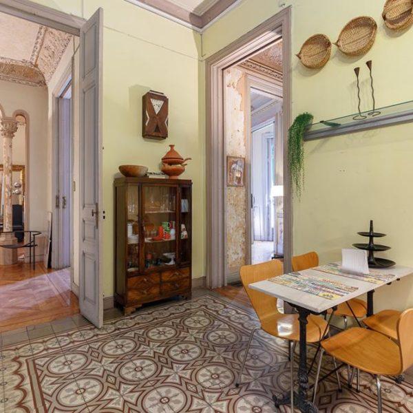 A cozinha tem piso em ladrilhos hidráulicos, cristaleira de época e cadeiras Arne Jacobsen