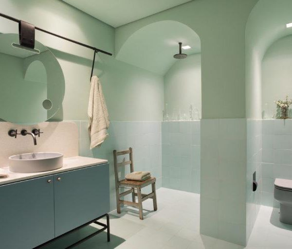 O banheiro tem meia parede revestida e aberturas em arcos, super tendência