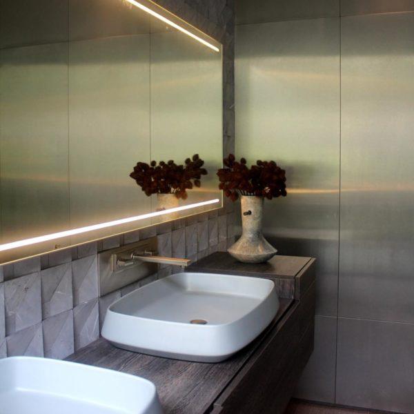 A parede de material metalizado confere charme extra ao banheiro, de linhas simples e sóbrias