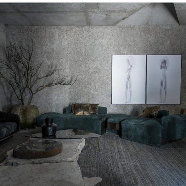 Sofá azul petróleo sobre base, piso e paredes em cinza. A maciez do tecido do sofá faz contraste com a textura do piso e das paredes. O ambiente de Neves merece ser visto/vivido com calma