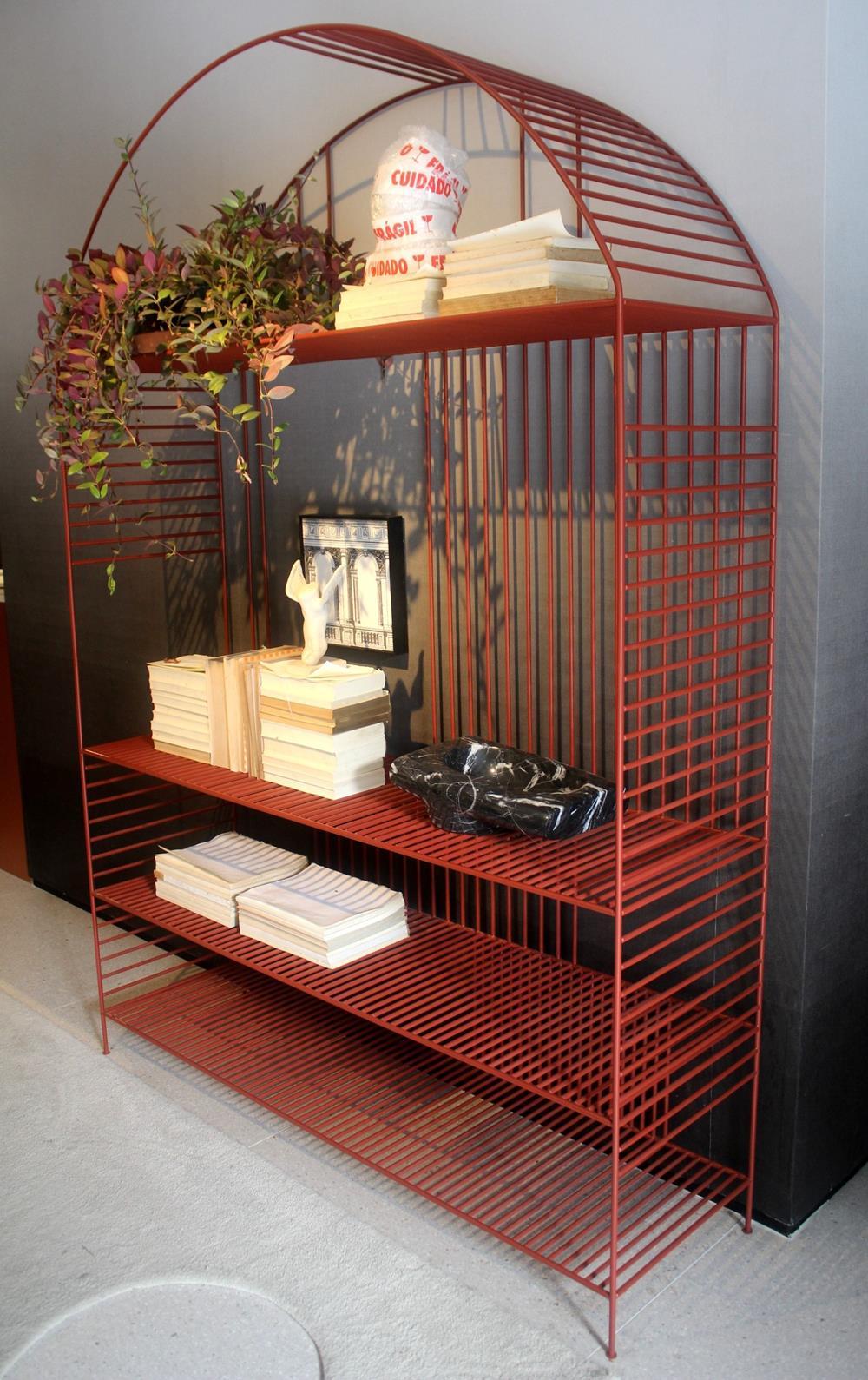 A estante em ferro vermelha é ponto focal no ambiente onde imperam cores pastéis