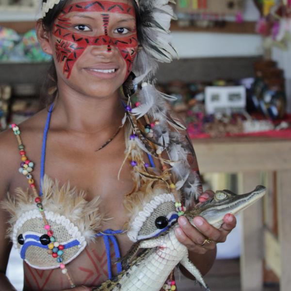 No passeio pelo Rio Negro, uma índia linda e corajosa segura um jacarézinho