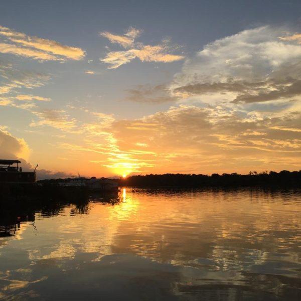 À esquerda, a silhueta do Jacaré Açu, barco do Mirante do Gavião que pode ser locado para viagens de 04 ou 06 dias pelo rio