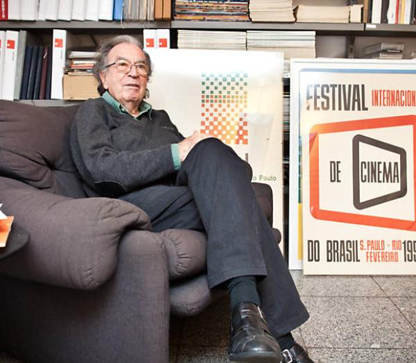 Wollner em sua casa em São Paulo, posa ao lado de alguns cartazes assinados por ele
