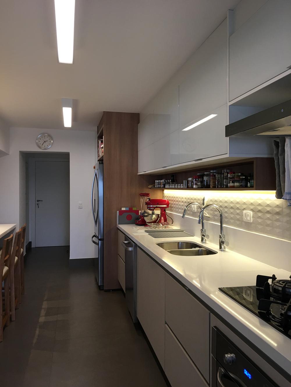 Cozinha de apartamento nos Jardins, integrada a sala de jantar, e pode ser fechada com grandes portas de correr
