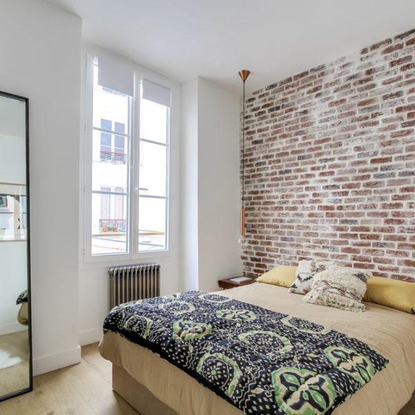 A parede de tijolinhos faz as vezes de cabeceira. As luminárias pendentes liberam espaço nas mesas de cabeceira