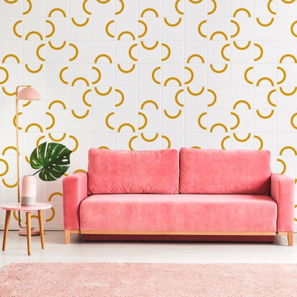 Pink couch between plant and lamp in bright living room interior with patterned wall. Real photo