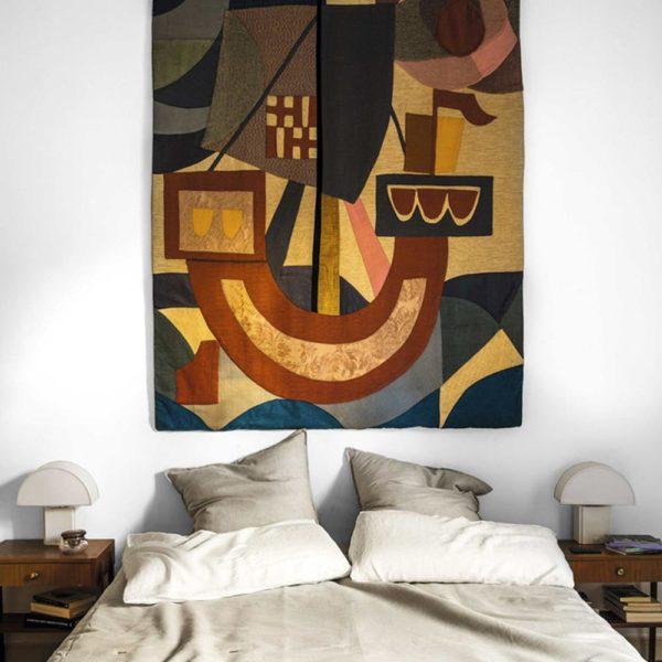 A obra de arte faz, sozinha, a decoração do quarto. A tapeçaria francesa dos anos 1950 é da Josephine House, assim como as luminárias anos 1970, de Hervé Guzzini