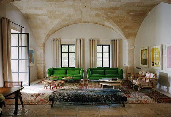 Os sofás verdes fazem interlocução perfeita com as características originais do imóvel.