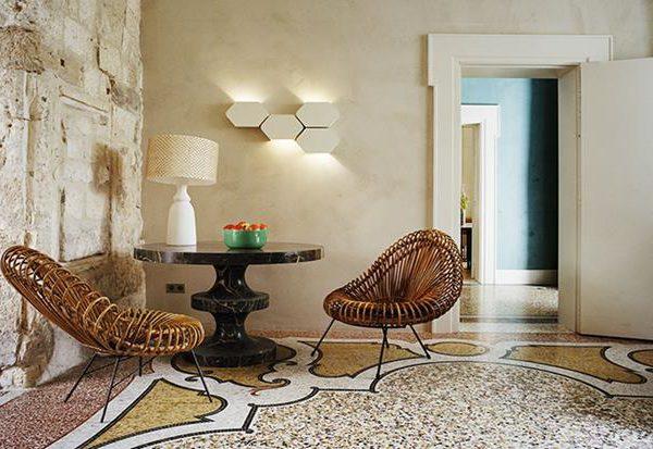 As formas sinuosas do desenho do piso se misturam ao brutalismo da parede com naturalidade, como se fossem feitos um para o outro.