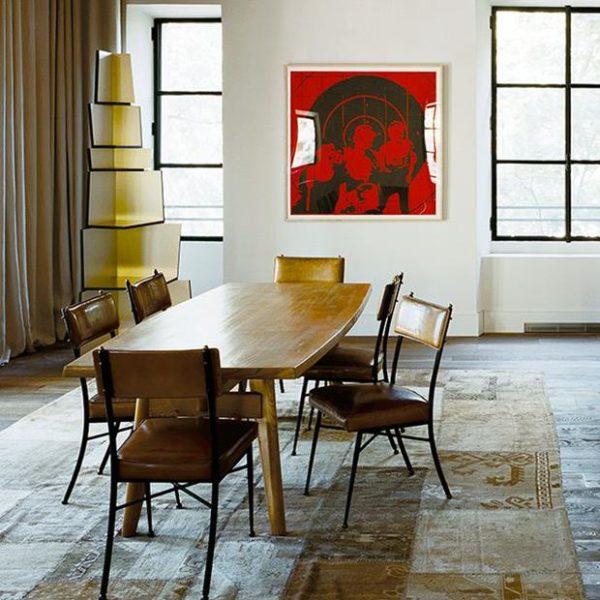 Conjunto de mesa e cadeiras de época sobre tapete de retalhos persa contrastam com obras de arte contemporâneas.