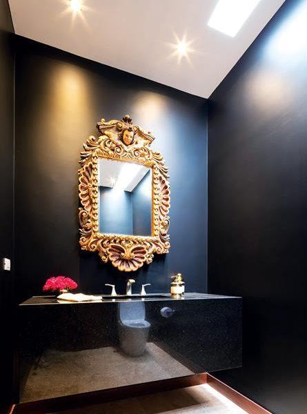 O lavabo tem paredes pretas, como outros aposentos da casa. Ao contrário do que pode parecer, o preto é muito chique e fica ótimo em vários estilos de decoração