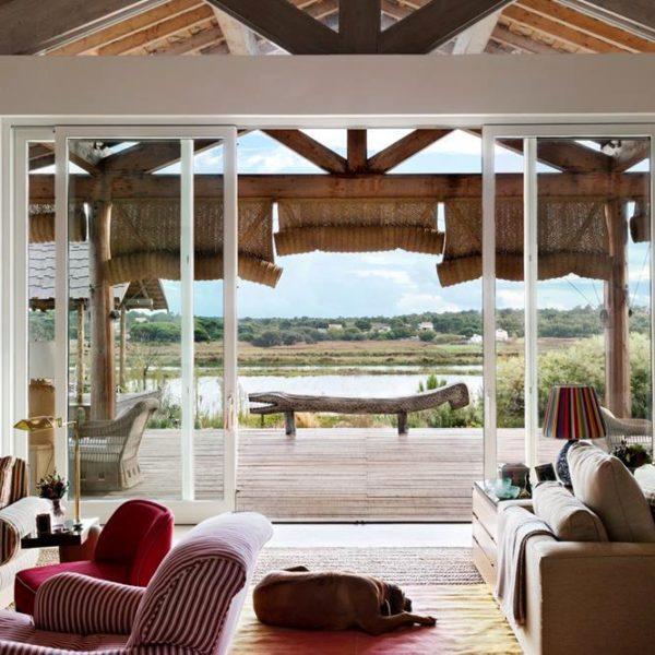 Poltronas revestidas com tecido listrado Claremont acomodam visitas e moradora para apreciarem a bela vista