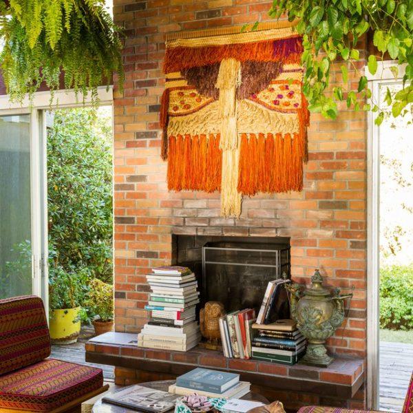 A tapeçaria e as plantas dão o clima de descontração. Sofá Michel Ducaroy
