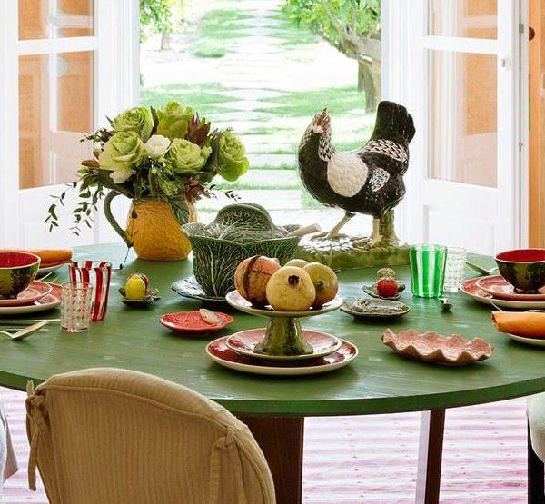A mesa posta com louça Bordallo Pinheiro, tradicional porcelana portuguesa, acomodada com vista para as videiras
