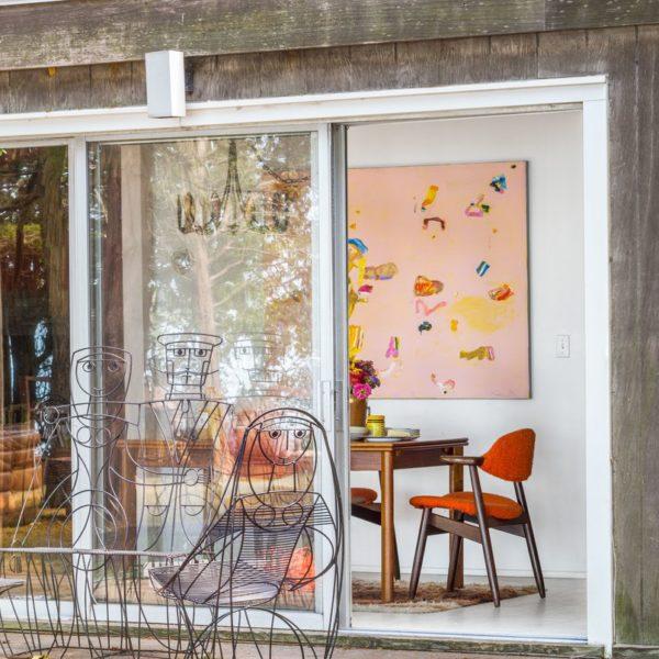 Cadeiras peculiares que evocam formas humanas ficam no deck de madeira, enquanto o interior apresenta explosões de cores em torno de uma pequena mesa com cadeiras vintage e uma pintura colorida