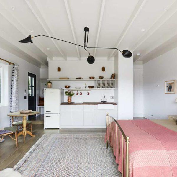 Nessa ampla garagem foi possível instalar uma mini cozinha, o que deixa o hóspede ainda mais a vontade. Os tons claros tem como complemento uma luminária linda e roupa de cama em tons médios/quase suaves.