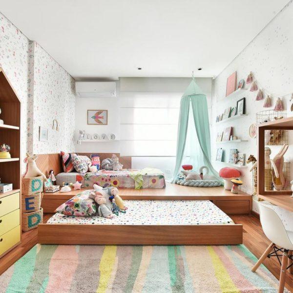 Uma plataforma que ocupa toda a parede abriga a cama e a bicama, o que libera espaço para brincadeiras